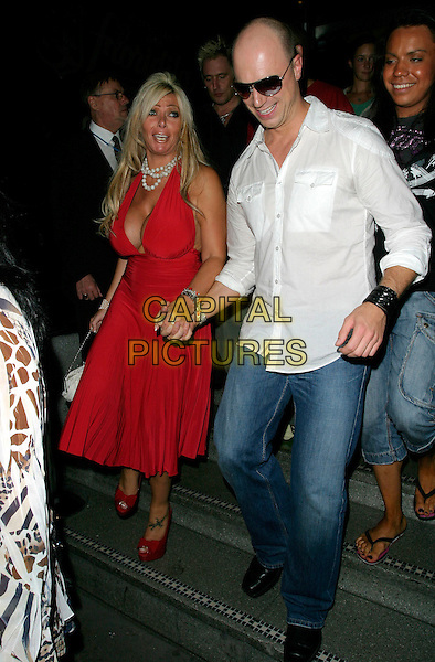 "LEA WALKER & RICHARD NEWMAN.At the UK Film Premiere of ""You, Me & Dupree"",.Odeon Leicester Square, London, England, .August 22nd 2006..full length big brother 7 red halterneck dress low cut cleavage fake boobs breasts plastic surgery pearl necklace beads bracelet platform shoes bag holding hands sunglasses white shirt ""Dickie & Dolly"" .Ref: AH.www.capitalpictures.com.sales@capitalpictures.com.©Adam Houghton/Capital Pictures."