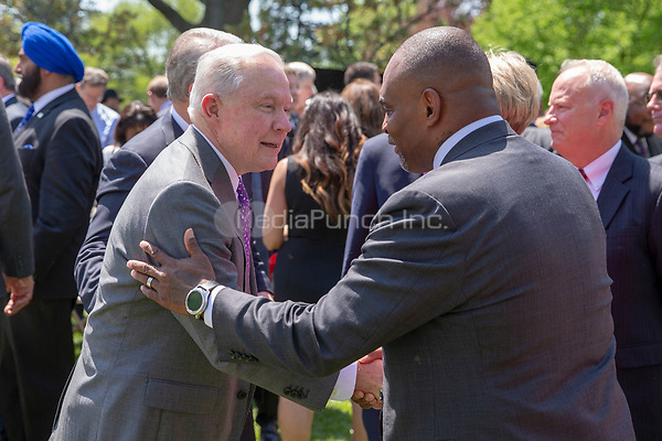 Attorney General Jeffrey Sessions greets a guest after a National Day of Prayer event in the Rose Garden at the White House in Washington, DC on May 3, 2018. Credit: Alex Edelman / CNP /MediaPunch