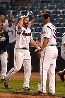 Nashville Sounds outfielder Kevin Mattison (2) high fives pitching coach Fred Dabney (38) after a walk off home run during a game against the Omaha Storm Chasers on May 19, 2014 at Herschel Greer Stadium in Nashville, Tennessee.  Nashville defeated Omaha 5-4.  (Mike Janes/Four Seam Images)
