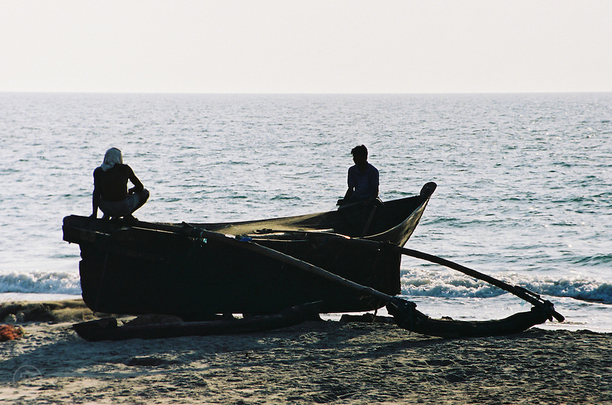 Fishermen working on traditional fishing boats on the beach in Goa.