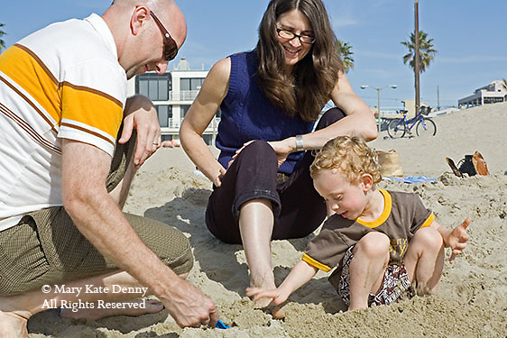 Three year old white boy plays in sand with Dad digging with shovel and Mom.pushing her toes in sand in Venice Beach, California