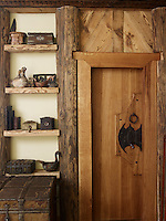 A contemporary wooden door with a creative handle has been inset into the rustic wooden wall covering