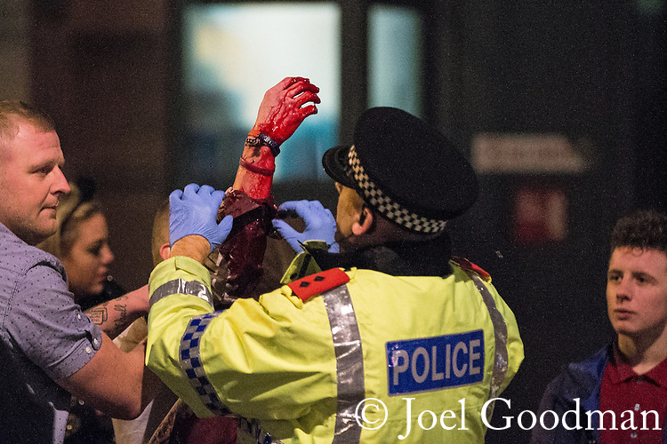© Joel Goodman - 07973 332324 . 21/12/2013 . Manchester , UK . A police Inspector tends to a man with a bleeding arm following a fight on the city's Charlotte Street . Christmas revellers out in the rain in Manchester on Mad Friday , the last Friday night before Christmas which is typically one of the busiest nights of the year for police and ambulance crews . Photo credit : Joel Goodman