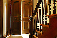 Sunlight beaming onto entrance and iluminating the oak wooden staircase of a historic residence in Naperville, IL.