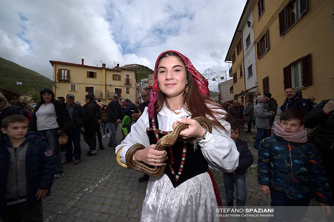 "Children of Cocullo with snakes in hand before the procession.The feast of snakes. Process dedicated to the Saint Dominic, in the streets of Cocullo, in the Abruzzo region, Italy on May 1, 2019.<br /> <br /> <br /> <br /> The St. Domenico's procession in Cocullo, central Italy. Every year on the first  of May, snakes are placed onto the statue of St. Domenico and then the statue is carried in a procession through the town. St. Domenico is believed to be the patron saint for people who have been bitten by snakes:<br /> <br /> Italy, Cocullo, in the Province of L'A...quila, is at 870 meters a.s.l., along the railway line connecting Sulmona to Rome. The village rises alongside Mount Luparo (1327 meters) ""The valley opening in front of the village is surrounded by bare rocks, while on the other side, to the south, snow-capped mountain crests follow one after the other...""<br /> San Domenico Abate lived in the 10th and 11th centuries AD. Born in Foligno, in the Umbria region, he started his pilgrimages, preaching and ascetic practices in Central Italy, making miracles recorded by the word-of-mouth tradition. He died on 22 January 1031 and was buried in Sora.<br /> <br /> Cocullo snake charmers are over with their snake hunting. They proceeded through the During the procession on the first in May, before the snakes are placed all over the statue of St. Dominick, they will be fed with milk kept in containers with crusca. It is the snake that, most of all other elements, expresses an ancestral myth: the unknown aspect and unpredictability of the natural environment with man's innate need to achieve the dominance on his own habitat. <br /> <br /> Snakes and wolves were the emblems of Italic peoples like the Marsians and Irpinians. Some areas in Abruzzo, especially in the Sagittario valley, were under the menace of wolves and snakes, which for the local populations represented the uncertainty and anxiety of their existence that, together with the precariousness and hardships of life, were almost unbearable. Therefore the community adopted s"