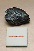 Specular hematite and a streak plate with the diagnostic red streak. Hematite, the primary ore of iron, ranges from red to black, but a streak test will always show the same hue of red.