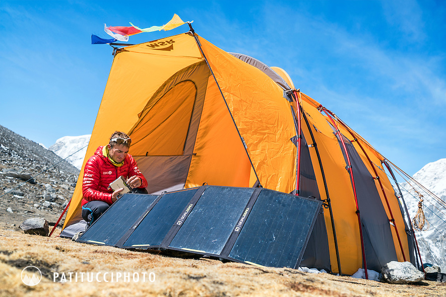 Ueli Steck at basecamp using solar panels to power all kinds of technology during the climbing expedition to the 8000 meter peak Shishapangma, Tibet