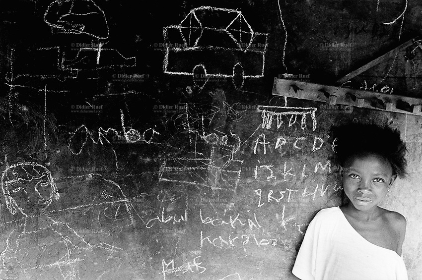"Guinea. State of ""Guinée Forestière"". Massakoundou. Camp for Sierra Leoneans refugees. Young girl in front of her house. Chalk drawings on the wall used as a blackboard. © 2001 Didier Ruef"