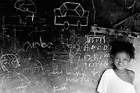 """Guinea. State of """"Guinée Forestière"""". Massakoundou. Camp for Sierra Leoneans refugees. Young girl in front of her house. Chalk drawings on the wall used as a blackboard. © 2001 Didier Ruef"""