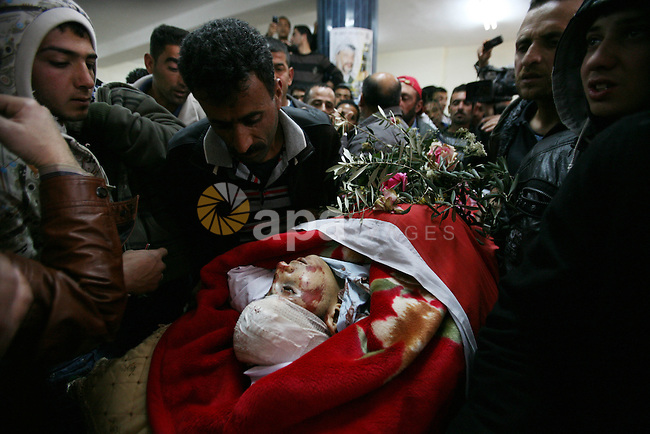 Palestinians  looks the body of Zakariya Abu Eram during his funeral in the West Bank town of Yatta, near Hebron, Friday, March 9, 2012. According to the Israeli military, a Palestinian stabbed an Israeli soldier in the neck during a raid in the town of Yatta, seriously wounding him. The soldier opened fire, wounding the assailant and killing Eram who was not involved in the attack, witnesses said. The Israeli military claim he was the attackers accomplice.  Photo by Mamoun Wazwaz
