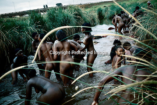 SOWETO, SOUTH AFRICA MARCH 11: Zulu maidens wash themselves in a river on March 11, 2005 in Soweto, Johannesburg, South Africa. About fifty girls celebrated their virginity by marching trough the streets of the township. Soweto is South Africa?s largest township and it was founded about one hundred years to make housing available for black people south west of downtown Johannesburg. The estimated population is between 2-3 million. Many key events during the Apartheid struggle unfolded here, and the most known is the student uprisings in June 1976, where thousands of students took to the streets to protest after being forced to study the Afrikaans language at school. Soweto today is a mix of old housing and newly constructed townhouses. A new hungry black middle-class is growing steadily. Most residents work in Johannesburg but the last years many shopping malls has been built, and people are starting to spend their money in Soweto. (Photo by Per-Anders Pettersson)