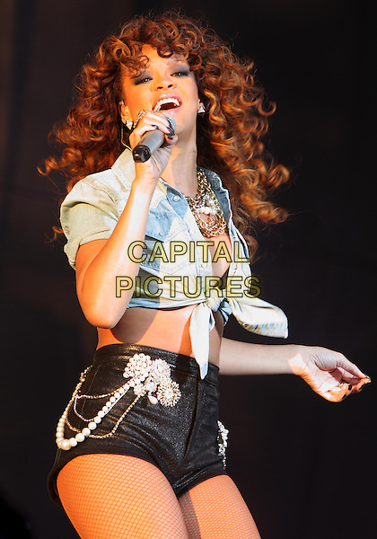 Rihanna (Robyn Rihanna Fenty).Rihanna performs at Day Two V Festival at Hylands Park, Chelmsford, Essex, England..August 21st, 2011.stage concert live gig performance music half length denim knotted shirt belly stomach midriff micro shorts black pearls brooch fishnet stockings singing necklaces .CAP/ROS.©Steve Ross/Capital Pictures