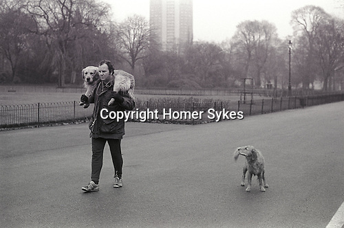 Man walking with dog Hyde Park London UK