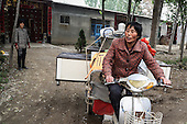 Chen Hua, 50, moves out of a village accommodation for her new urban home in northeastern China.<br /> <br /> Her former village house was bulldozed by the government three years ago to make way for high-rise development. <br /> <br /> In the four years between her rural home being razed and the completion of her new city apartment, she and her family lived in temporary village housing such as this one. <br /> <br /> China is pushing ahead with a dramatic, history-making plan to move 100 million rural residents into towns and cities over the next six years &mdash; but without a clear idea of how to pay for the gargantuan undertaking or whether the farmers involved want to move.<br /> <br /> Moving farmers to urban areas is touted as a way of changing China&rsquo;s economic structure, with growth based on domestic demand for products instead of exporting them. In theory, new urbanites mean vast new opportunities for construction firms, public transportation, utilities and appliance makers, and a break from the cycle of farmers consuming only what they produce.<br /> <br /> Urbanization has already proven to be one of the most wrenching changes in China&rsquo;s 35 years of economic reforms. Land disputes rising from urbanization account for tens of thousands of protests each year.