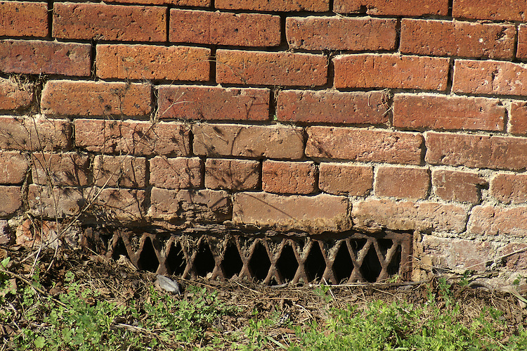 An old crawl space vent grate serves its function with more flair that its modern counterparts.