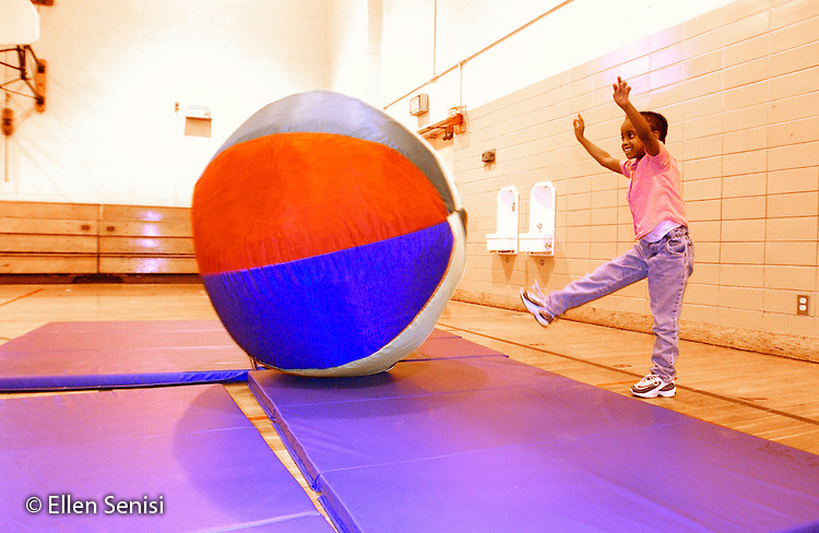 MR / Schenectady, NY                                  .Yates Arts-in-Education Magnet School (urban school).Pre-Kindergarten class; NYS Universal Pre-K Program.Girl (5, African-American) kicks big ball in gym class..Smi14.Color and light manipulated  digitally..©Ellen B. Senisi