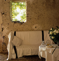 A sofa and table covered in Irish linen in the summer dining area in the converted barn