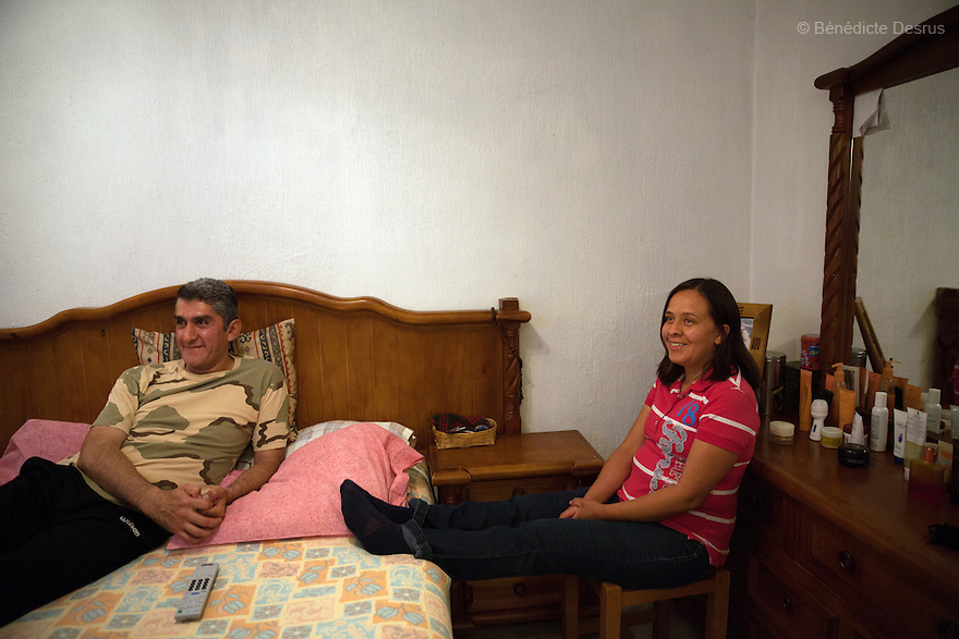 "Donovan watches television with his wife in their bedroom at home in Texcoco, Mexico on May 21, 2015. Donovan Tavera, 43, is the director of ""Limpieza Forense México"", the country's first and so far the only government-accredited forensic cleaning company. Since 2000, Tavera, a self-taught forensic technician, and his family have offered services to clean up homicides, unattended death, suicides, the homes of compulsive hoarders and houses destroyed by fire or flooding. Despite rising violence that has left 70,000 people dead and 23,000 disappeared since 2006, Mexico has only one certified forensic cleaner. As a consequence, the biological hazards associated with crime scenes are going unchecked all around the country. Photo by Bénédicte Desrus"