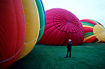 Retro image of the Walla Walla Balloon festival with person holding rope surrounded by colorful balloons as they inflate before liftoff sunrise Walla Walla Eastern Washington State USA