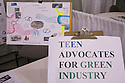 Teen Advocates for Green Industry sign with a poster about worldwide recycling markets in the background. West Coast Green is the nation?s largest conference and expo dedicated to green innovation, building, design and technology. The conference featured over 380 exhibitors, 100 presenters, and 14,000 attendees. Location: San Jose Convention Center in Silicon Valley (San Jose, California, USA), September 25-27, 2008
