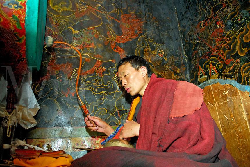 Buddhist Gelugpa monk bangs drum, with cymbals on knees, while reciting prayers at Drepung monastery, Lhasa, Tibet, China.