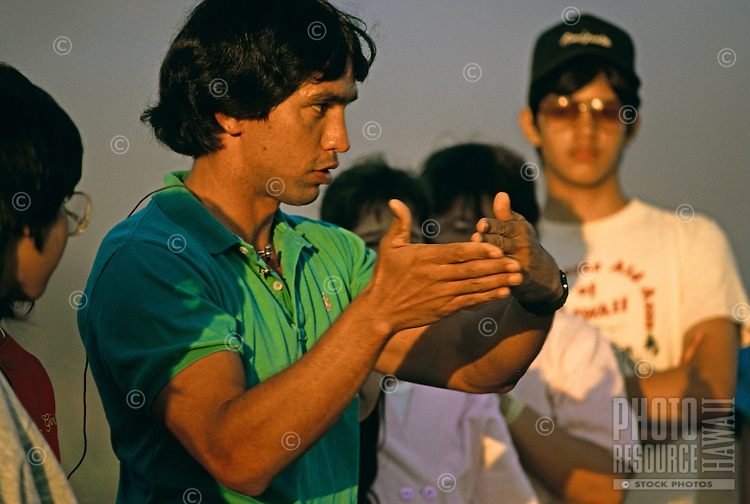 Navigator of Polynesian voyaging canoe, Hokule'a, Nainoa Thompson talks to students at heiau, Pokai Bay, Waianae, Oahu.