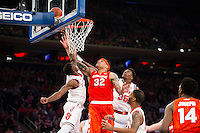 NEW YORK, NY - Sunday December 13, 2015: DaJuan Coleman (#32) of Syracuse goes hard to the rim against St. John's University as the two square off during the NCAA men's basketball regular season at Madison Square Garden in New York City.