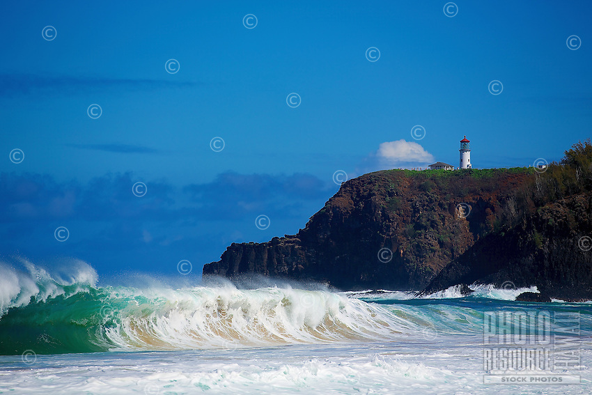 A giant wave falls onto Secrets Beach with the Kilauea Lighthouse and visitors in the distance, Kaua'i.