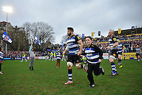Guy Mercer of Bath Rugby, mascot in hand, leads his team out onto the field. Aviva Premiership match, between Bath Rugby and Worcester Warriors on December 27, 2015 at the Recreation Ground in Bath, England. Photo by: Patrick Khachfe / Onside Images