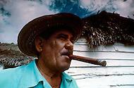 Cuba, 1992: A tabacco farmer  smoking a cigar outside his home near Vinales, Cuba.