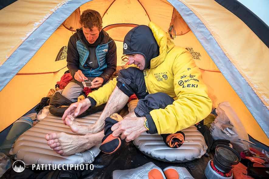 Ueli Steck and David Göttler inside advance basecamp tent after Shishapangma. Ueli is looking at his feet after removing them from his boots to be sure there is no sign of frostbite.