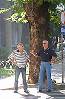 Two men standing talking discussing on a street corner under a big tree giving shade. Podgorica capital. Montenegro, Balkan, Europe.