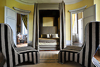 A four-poster bed stands between a pair of curved doors in this spectacular circular bedroom