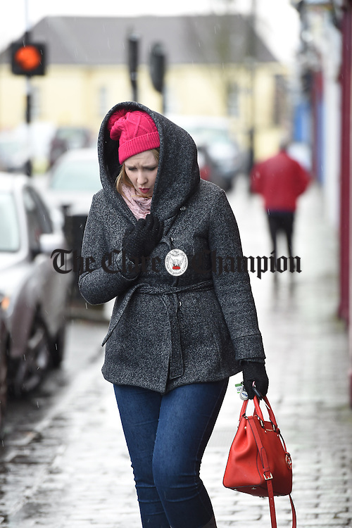 Lorraine Fitzpatrick hurriedly goes back to her car during a heavy downpour in Kilrush. Photograph by John Kelly.