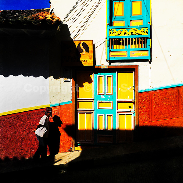 A Colombian peasant walks in front of a brightly painted colonial house in Jericó, a village in the coffee region (Zona cafetera) of Colombia, 23 April 2018.