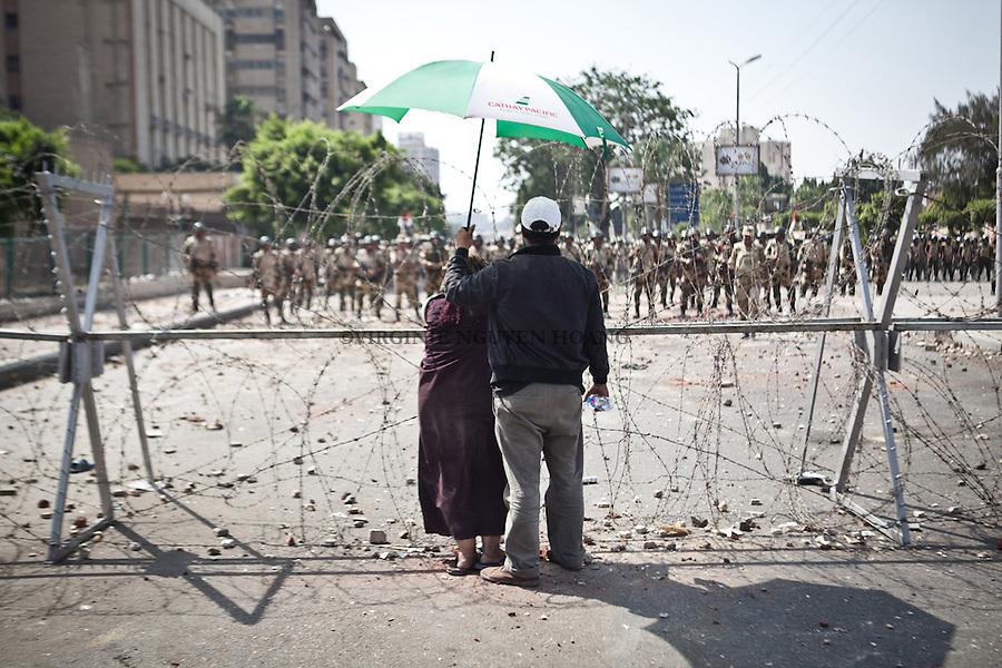 Un couple fixe des soldats de l'arm&eacute;e. Derri&egrave;re eux; un groupe de manifestants se trouve devant un deploiement de l'arm&eacute;e en face du b&acirc;timent de la garde pr&eacute;sidentielle &agrave; Nasr City. <br /> <br /> A couple is fixing army soldiers. Behind them, a group of protesters in front of a deployment of the army at the presidential guard building in Nasr City.