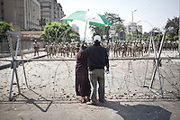 Un couple fixe des soldats de l'arm&eacute;e. Derri&egrave;re eux; un groupe de manifestants se trouve devant un deploiement de l'arm&eacute;e en face du b&acirc;timent de la garde pr&eacute;sidentielle &agrave; Nasr City. <br /> <br /> A couple is fixing army soldiers. Behind them, a group of protesters in front of a deployment of the army at the presidential guard building in Nasr City.
