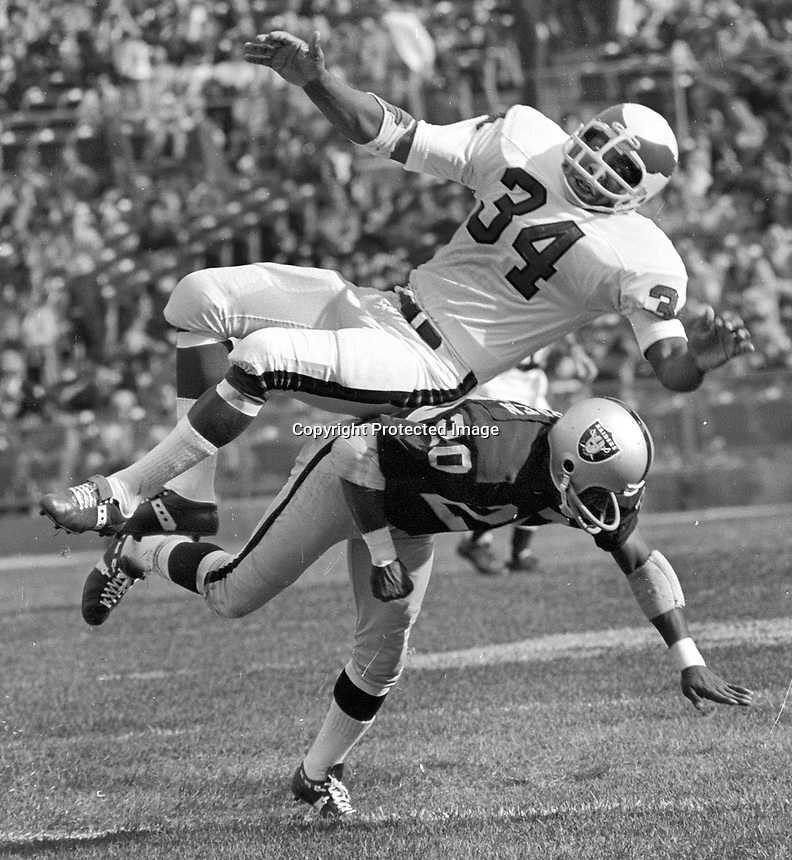 Philadelphia Eagles #34 Larry Watkins is upended by Oakland Raiders #20 Jimmy Warren .(1971 photo by Ron Riesterer)