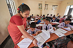 A teacher checks students' work in a classroom in Suihari in northern Bangladesh.