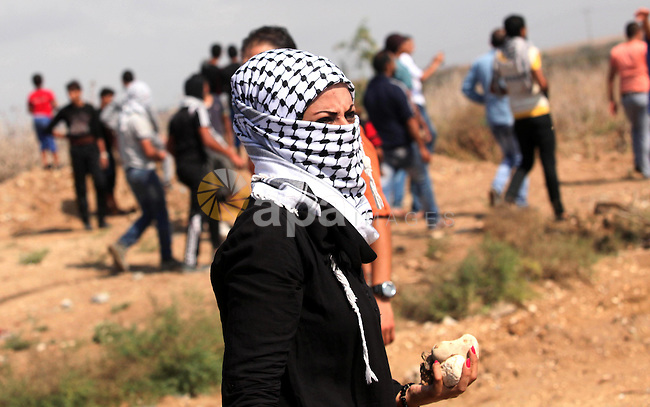A female Palestinian protester carries stones during clashes with Israeli security forces near the border fence between Israel and the Gaza Strip on October 9, 2015 east of Gaza City. Tension and protests rose after an Israeli man on 09 October stabbed four Palestinians in southern Israel, in what is being seen as a revenge attack, officials said. On 08 October several violent incidents happened, including stabbings which left eight Israelis injured, one Palestinian was killed in East Jerusalem and six in the Gaza Strip in clashes with the army while at least six were injured on the West Bank. Photo by Ashraf Amra