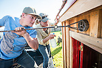 Ty Busi brands over the door with the Circle-B family brand as his mother Colett sprays water to keep it from burning.<br /> <br /> The Busi family and friends use hot irons to christen and brand the new pump shed at their corrals near Jackson, California.