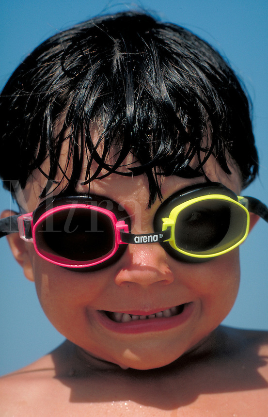Close up portrait of a grinning boy in colorful diving goggles. Alex. East Hampton.
