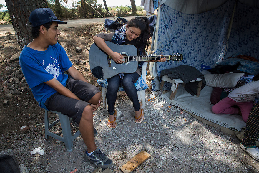Noh cousins playing music at Ritsona camp. The family, who are Yazidi, immigrated from Iraq due to the ISIS threat nearby. They are now stuck in Greece and living in Ritsona, a refugee camp outside of Athens. PHOTO BY JODI HILTON/PULITZER CENTER