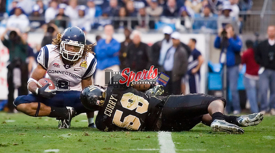 Connecticut tail back Andre Dixon (2) is tackled for a 1 yard loss by Wake Forest linebacker Aaron Curry (59) at the Meineke Car Care Bowl Saturday, December 29, 2007 in Charlotte, NC.