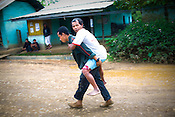 A disabled man is carried on the back by his relative after casting the vote in village Kumbi, Manipur, India. About 62 per cent of 8,02,000 voters exercised their franchise in an incident-free secondphase of Lok Sabha elections for the prestigious Inner Manipur parliamentary constituency on April 22nd 2009.