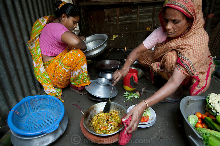 "Shahnaz Hossain Begum (left) shares cooking space with one of her tenants at her home in Bari Majlish village outside Dhaka, Bangladesh. (From the book What I Eat: Around the World in 80 Diets.)  The caloric value of her day's worth of food for a typical day in December was 2000 kcals. She is 38; 5' 2"" and 130 pounds. This mother of four was able to earn enough to build several rental rooms next to her home in her village of Bari Majlish, an hour outside Dhaka. She and her tenants share a companionable outdoor cooking space and all largely cook traditional Bangladeshi foods such as dahl, ruti (also spelled roti), and vegetable curries. She and her family don't drink the milk that helps provide their income."