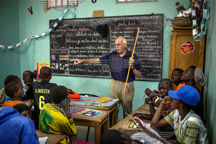 American volunteer Charles Horner teaching French to children at the Maison de la Gare, a charity that seeks to rehabilitate ex-Talibe (children who live and study the Koran at a Daara, religious school). <br /> Talibe often have issues that stem from being separated from their parents at a young age and the abuse they endure at the Daaras where they are expected to beg to raise money for the Daara's marabout and to get food to fed themselves.
