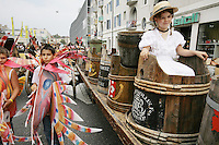 Switzerland. Canton of Neuchâtel. Neuchâtel. Grape Harvest Festival. The flower parade (corso) with its creative vehicles. A young girl, dressed with a white shirt and a hat, seats on a cart inside a barrel, used to collect grapes during the harvest. A group of young boys, dressed up with fishes outfits, walk on the road . © 2006 Didier Ruef