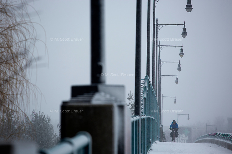 A woman rides a bike in Cambridge, Massachusetts, USA, as Winter Storm Nemo approaches on Friday, Feb. 8, 2013.