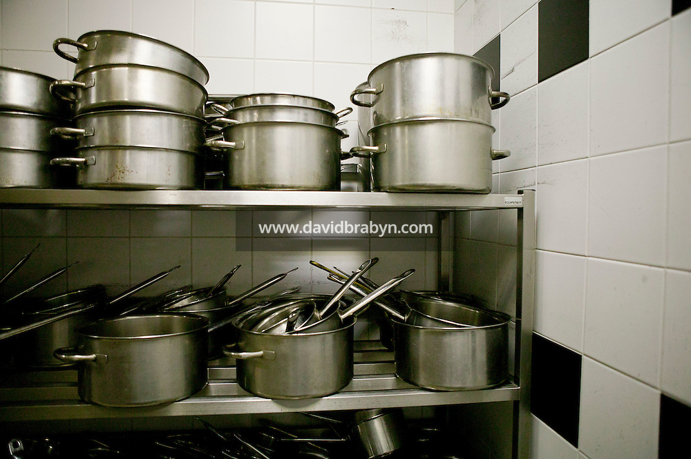 Metal pots, pans and saucepans sit on shelves in a in a storage room kitchen at the Gregoire Ferrandi cooking school in Paris, France, 17 December 2007.